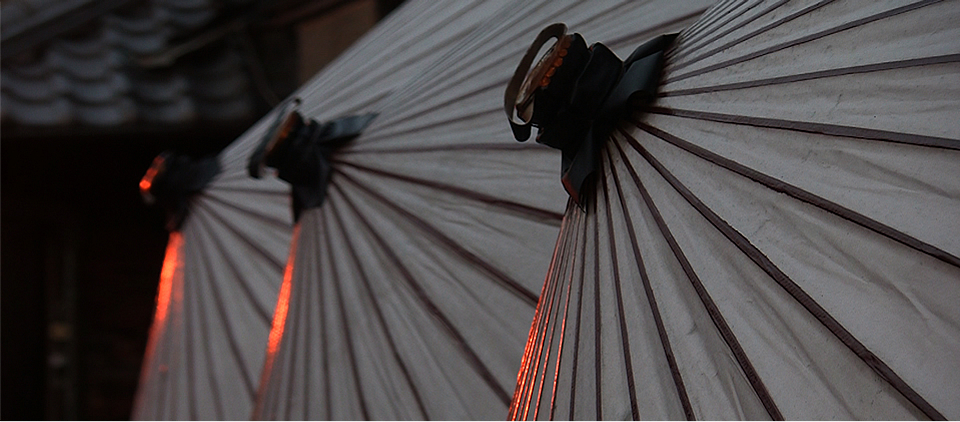 A photo from the documentary. Three 			        traditional japanese umbrellas.